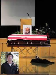 Hawkeye in front of casket